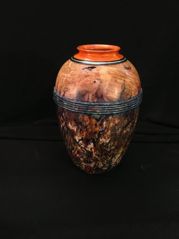 """""""Desert Urn"""" is the title of this 81/2"""" tall x 51/2"""" diameter hollow vessel I turned. It combines silver inlay into the pernambuco and ebony rim at the top.  I gilded the lower body of the vessel with silver leaf and did a patina finish over it."""