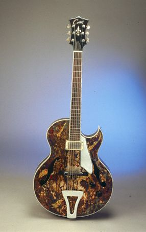 """This guitar was built by Tom Cerletti. This Collaborative project """"Cerletti / Marks"""", 17″ archtop model was built in 1999 for guitarist Steve Kimock, the guitar is made of German spruce and rock maple. The neck is Cuban cedar. The David J. Marks finish is of copper, silver and gold leaf; the chemical is patina, with Japan paint and lacquer."""